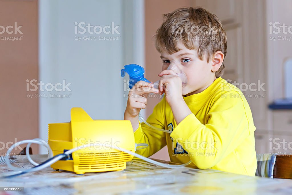 Kid boy playing with wooden balance toy at home stock photo