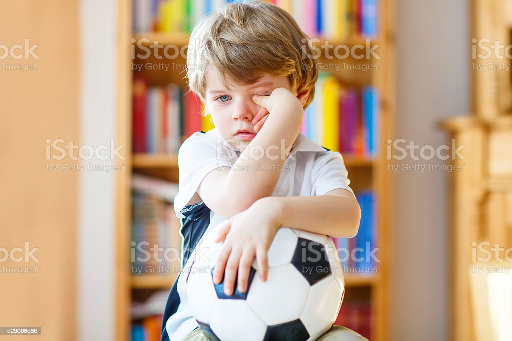 Kid boy sad about lost football or soccer game stock photo