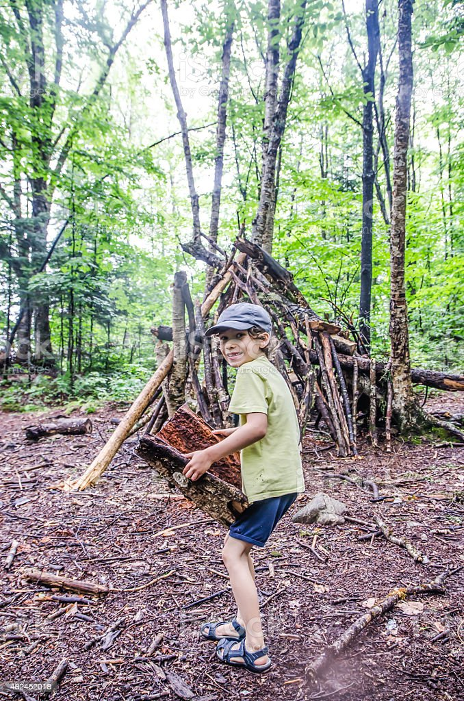 Kid building a shack in forest stock photo