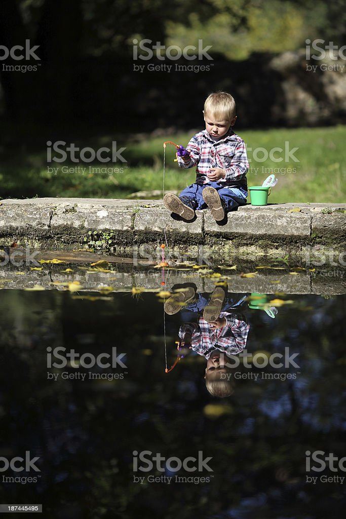 kid catches a fish pond in the mirror royalty-free stock photo