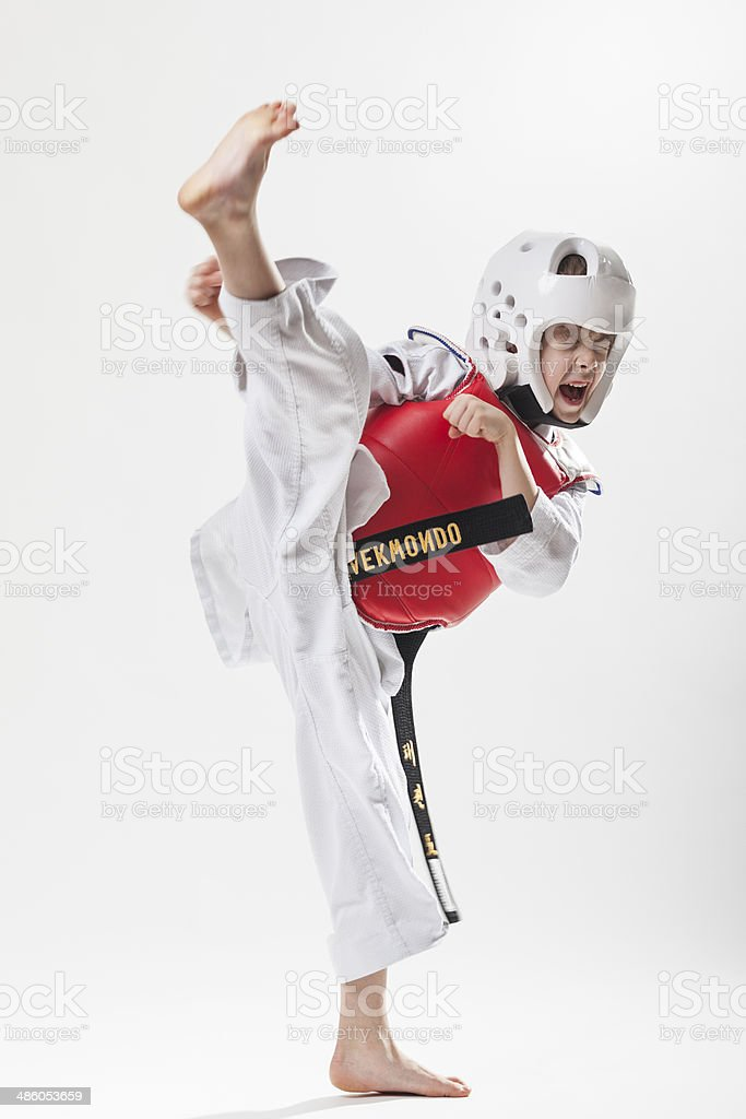 Kid doing tae kwon do high kick stock photo