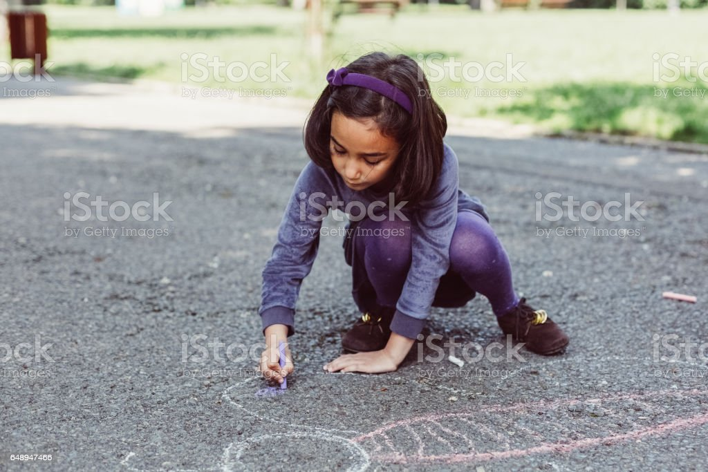 Kid drawing with chalk in the park stock photo