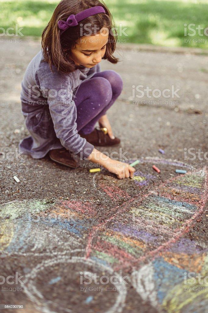 Kid drawing with chalk on asphalt stock photo