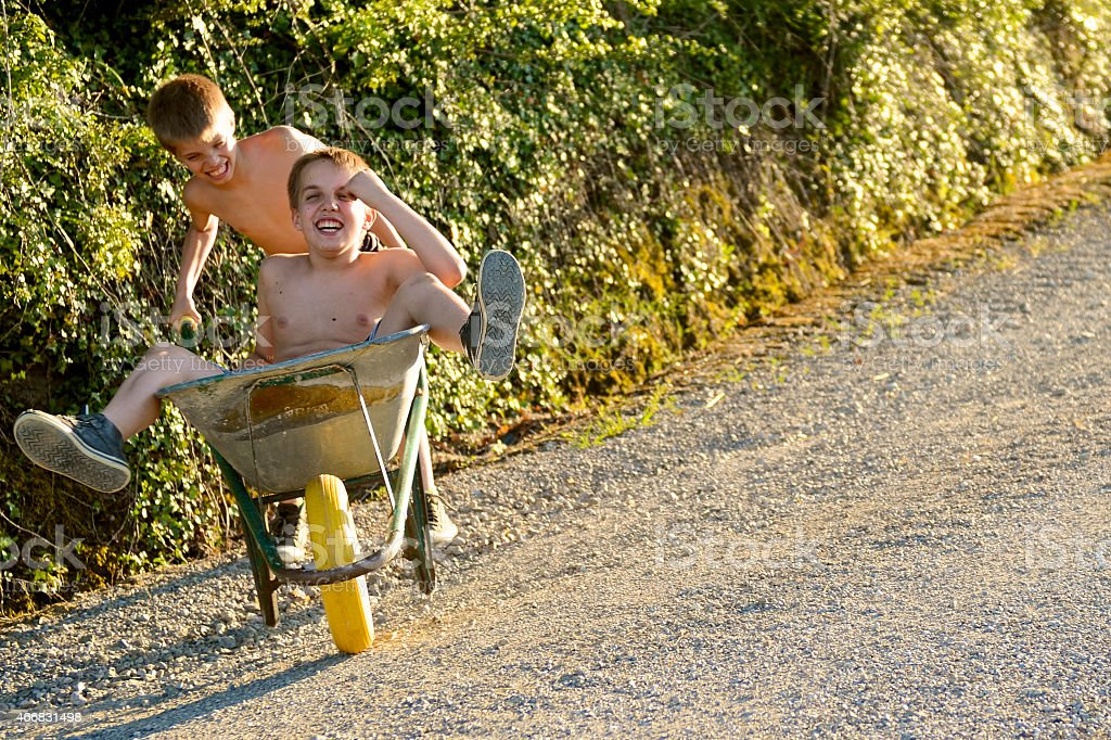 Kid  during wheelbarrow race in countryside stock photo