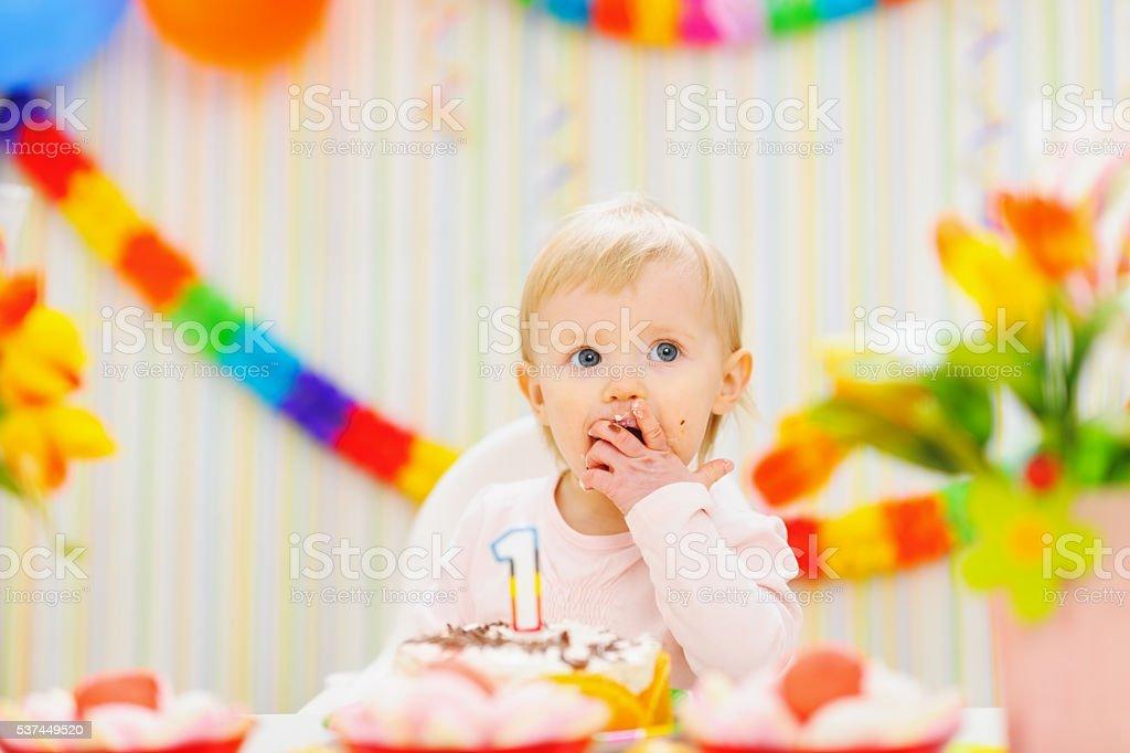 kid eating first birthday cake stock photo