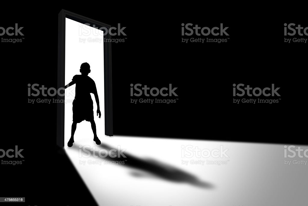 Kid Enters Dark Room Concept of Unknown and Fear stock photo