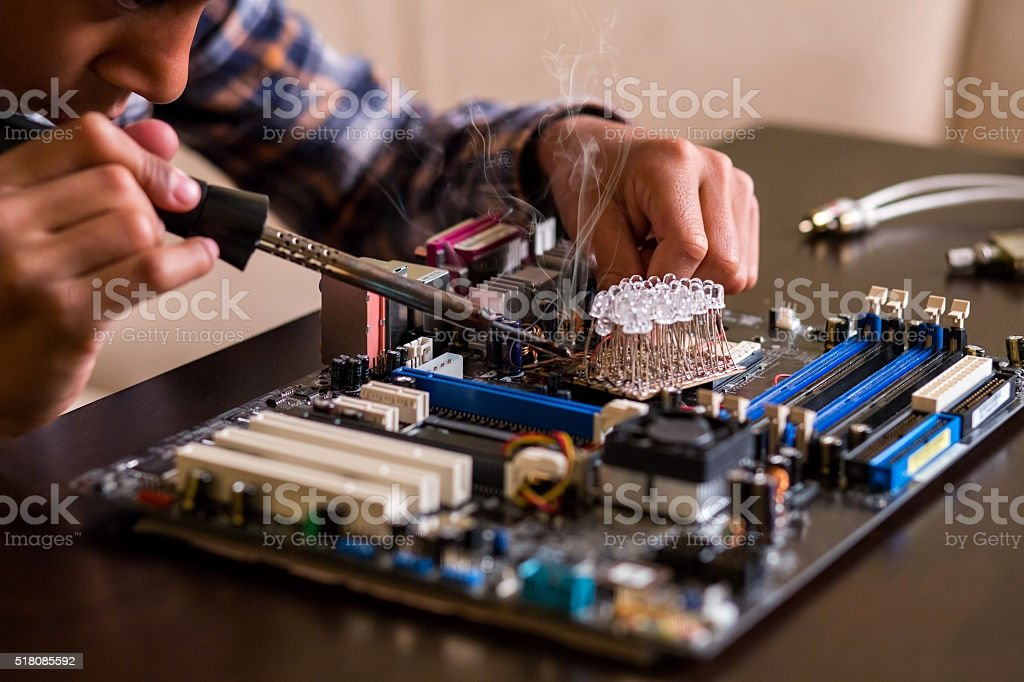 Kid fixes motherboard on table. stock photo