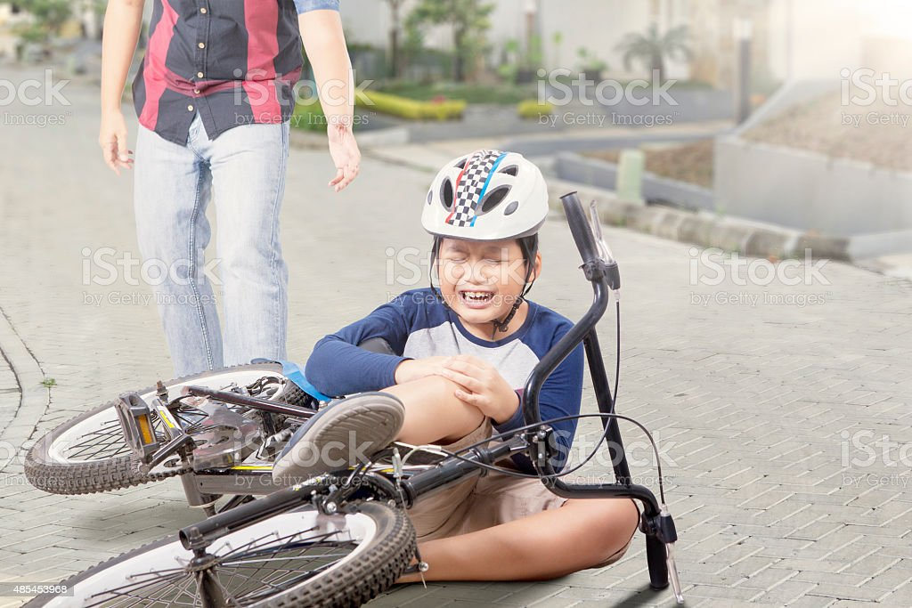 Kid gets accident with his bike and crying stock photo