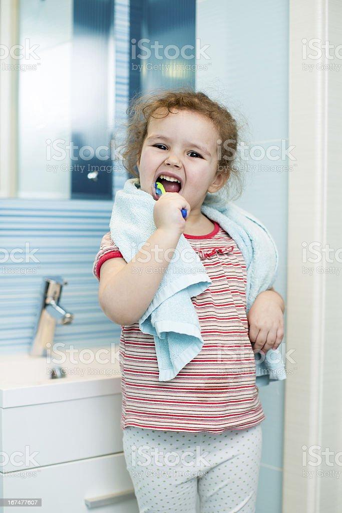 Kid girl brushing teeth in bathroom royalty-free stock photo