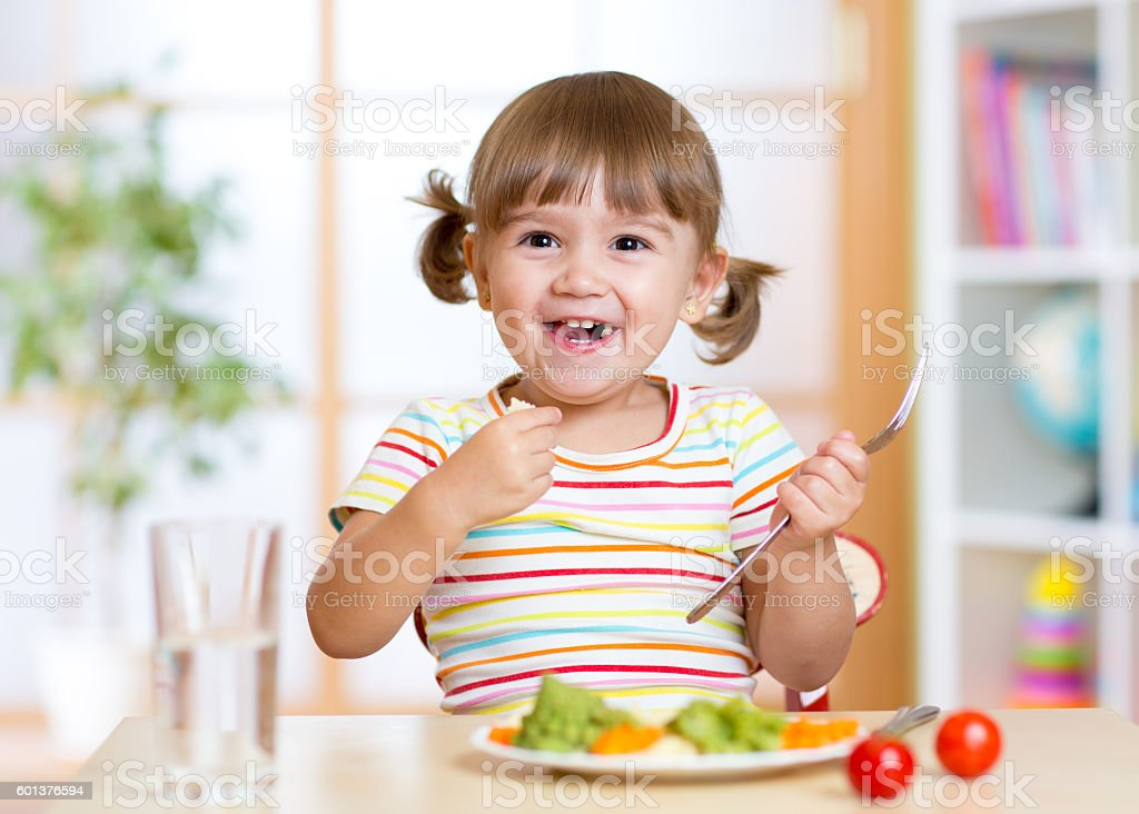 kid girl eating healthy vegetables - foto de acervo