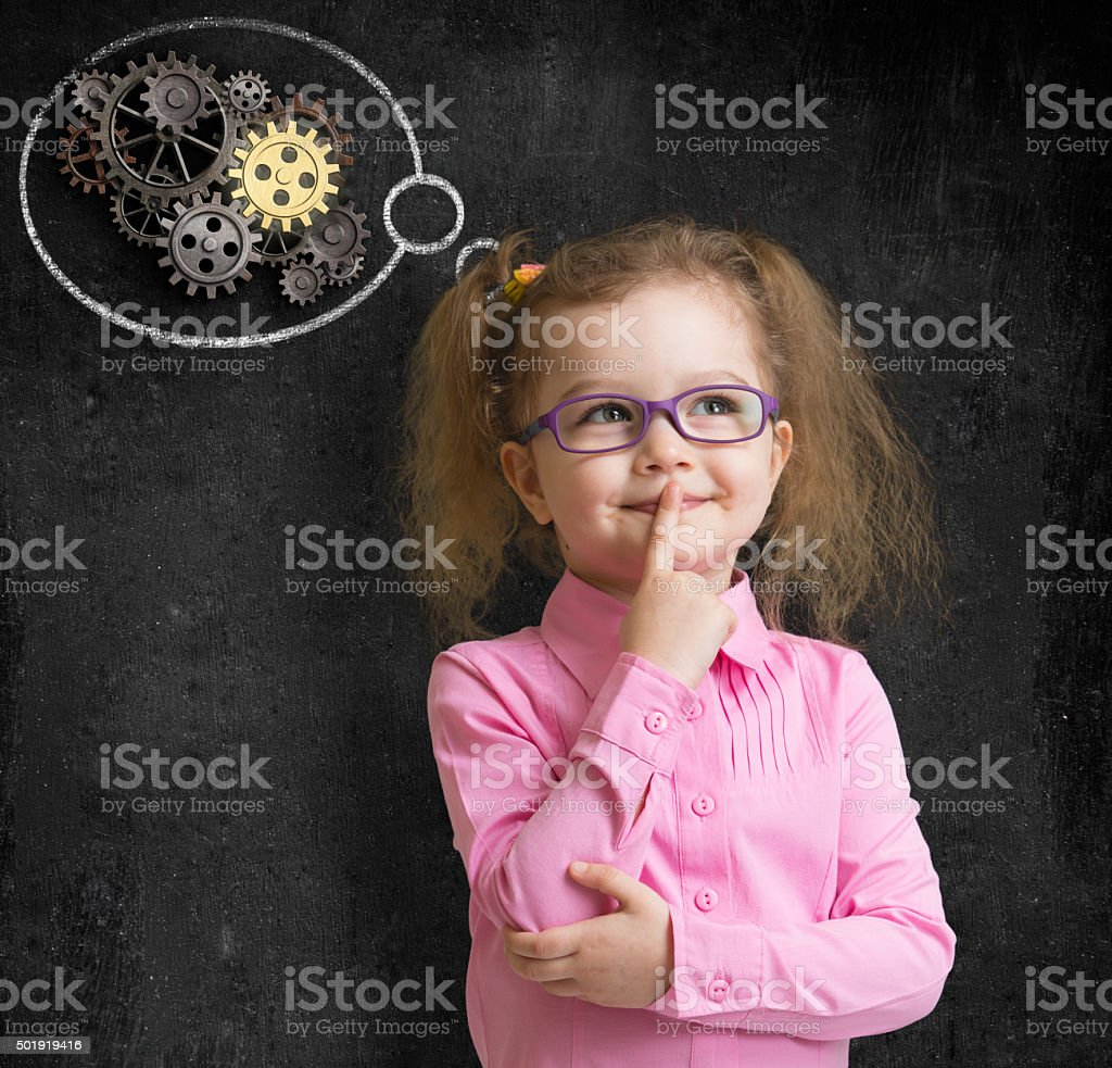 kid girl in glasses with bright idea standing near school stock photo