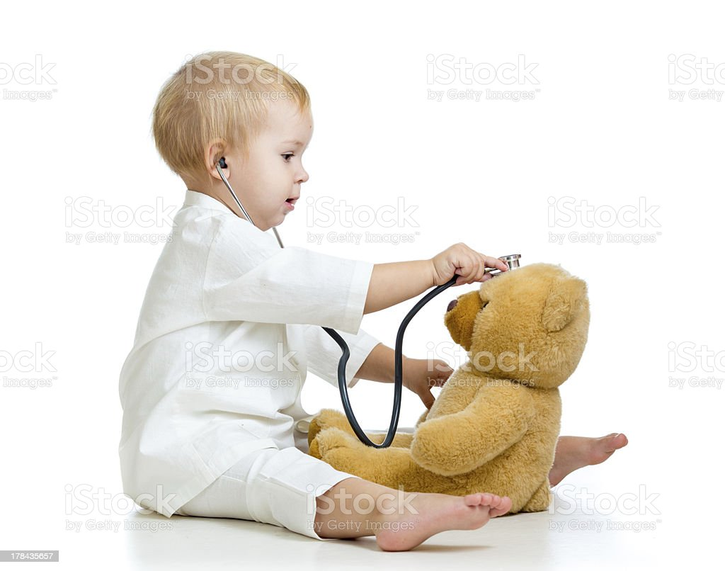 kid girl playing doctor with toy stock photo