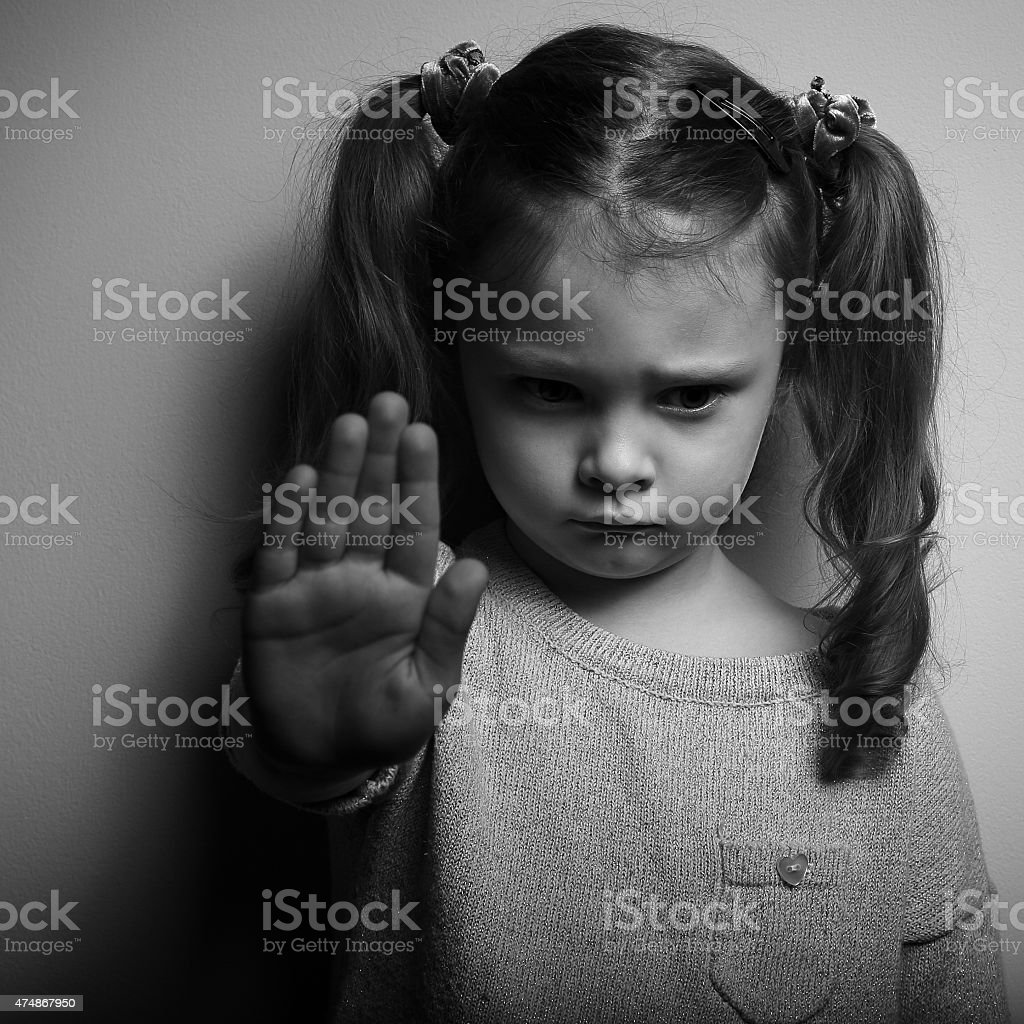 Kid girl showing hand signaling to stop violence stock photo