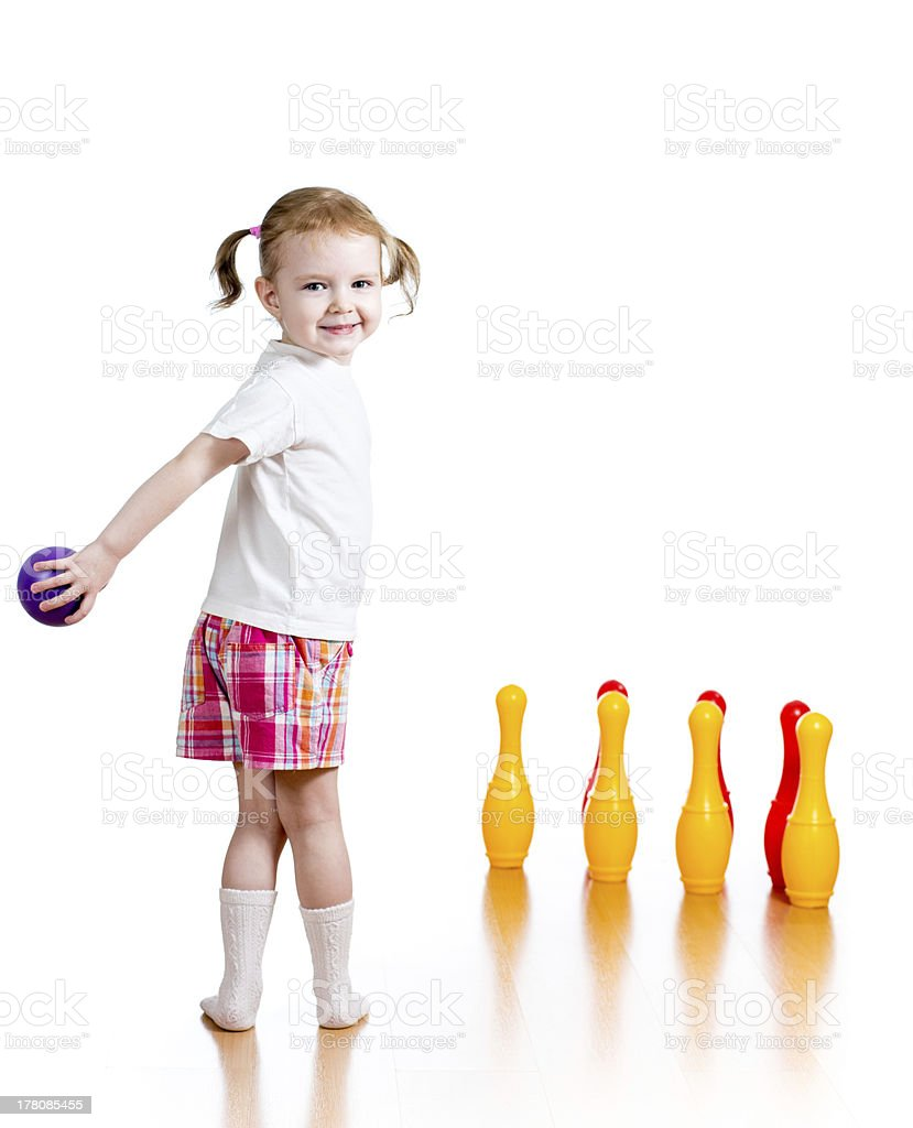 Kid girl throwing ball to knock down toy bowling pins stock photo