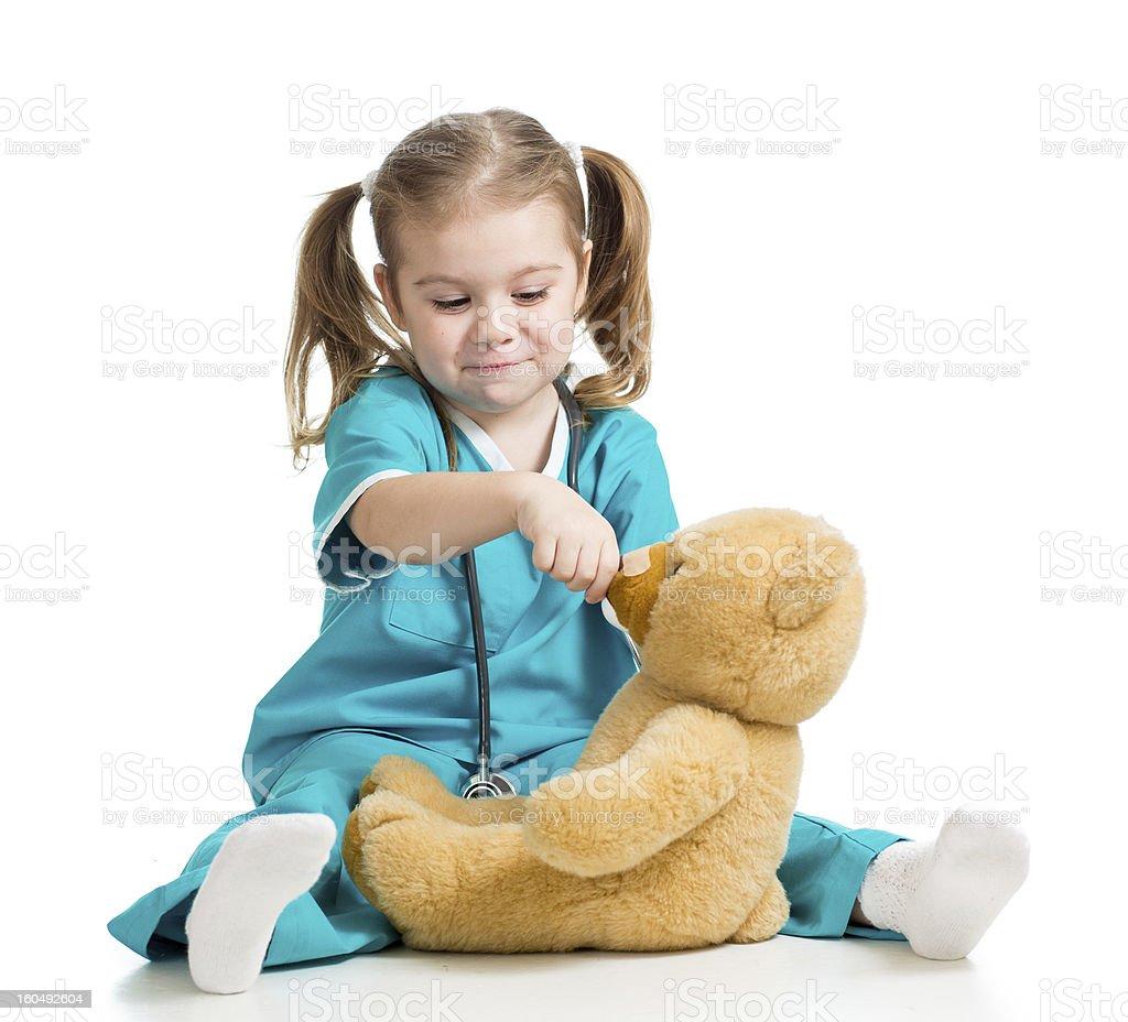 kid girl with clothes of doctor spoon feeding teddy bear stock photo