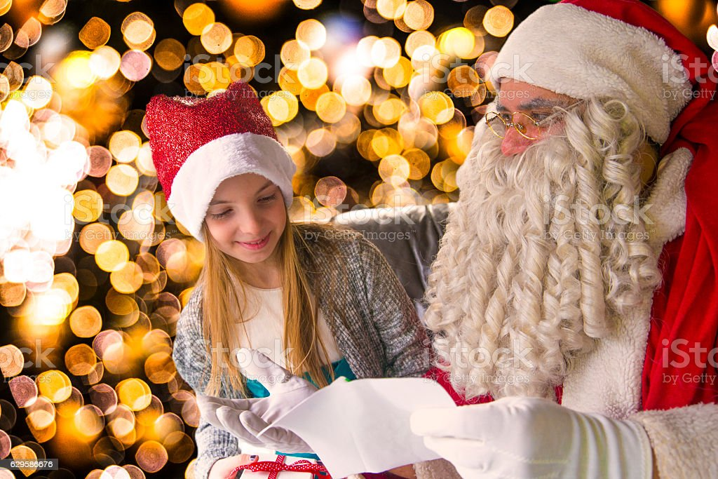 Kid going over naughty nice list with Santa stock photo