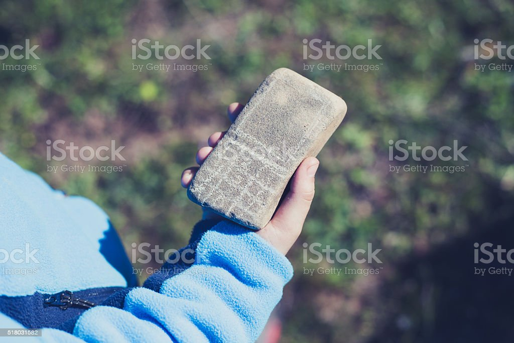 Kid hand holding a stone mobile phone. stock photo