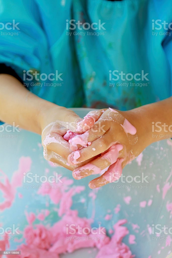 Kid hands playing with pink slime stock photo