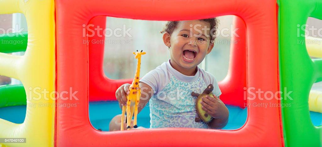Kid having fun in inflatable swimming pool. stock photo