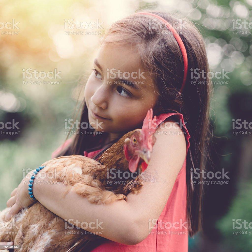 Kid holding a hen stock photo
