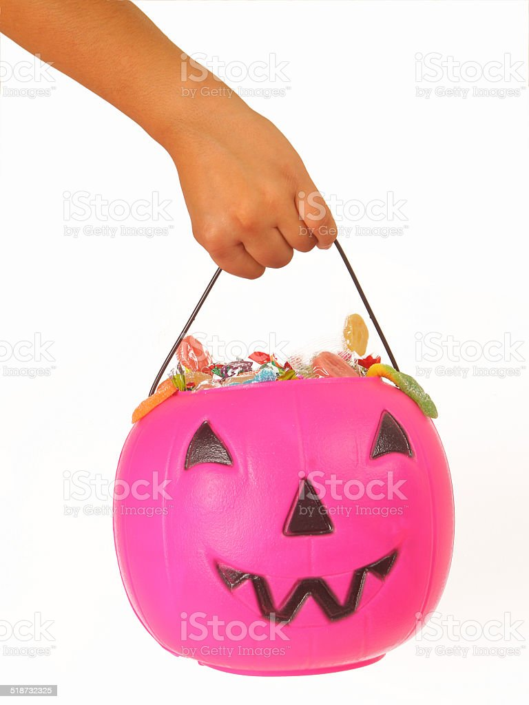 Kid holding a pink plastic pumpkin filled with candy stock photo