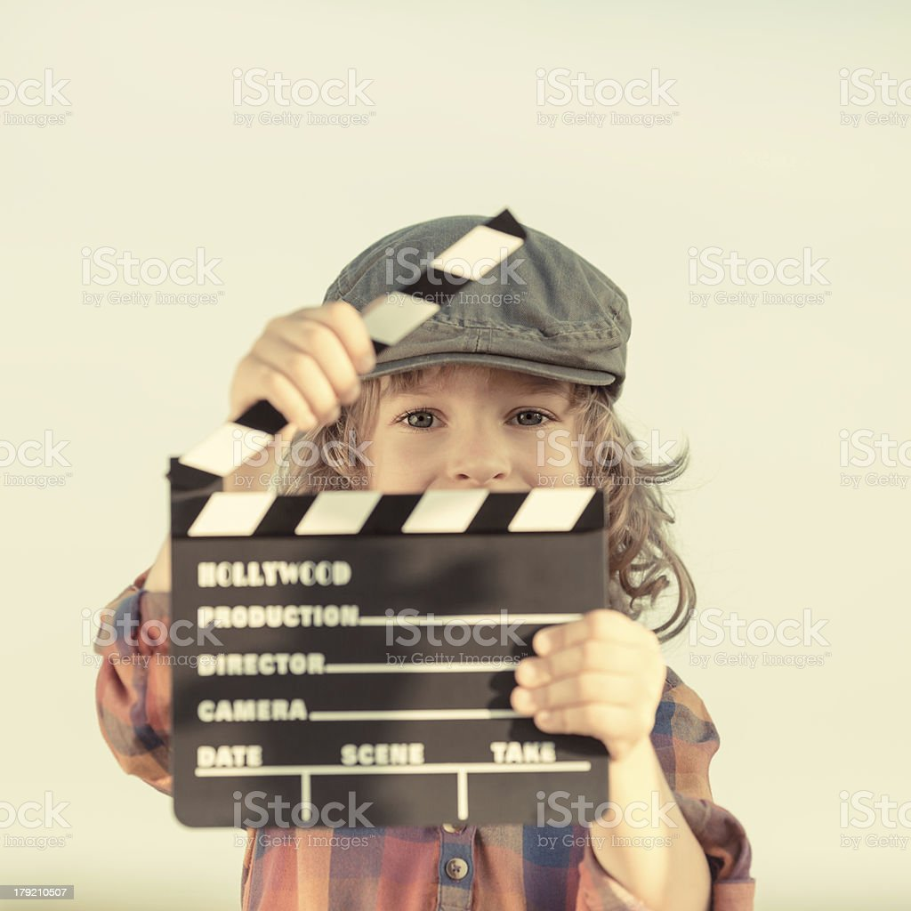 Kid holding clapper board in hands stock photo