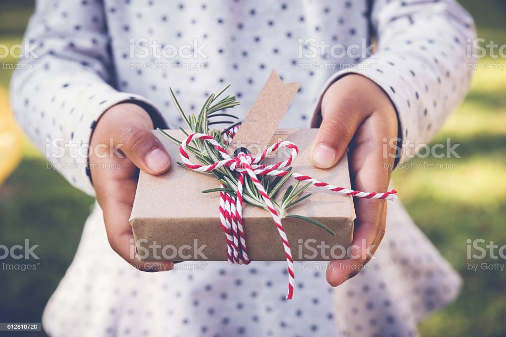 kid holding eco gift box with brown tag, holidays background stock photo