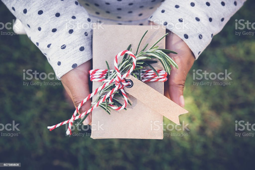 kid holding eco holidays gift box with brown tag stock photo