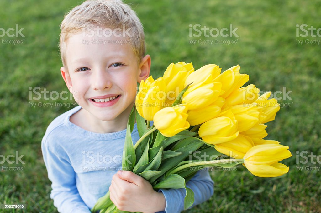 kid holding flowers stock photo