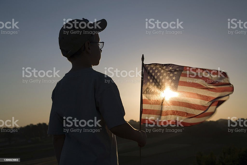 Kid holding the American flag against the sunset stock photo