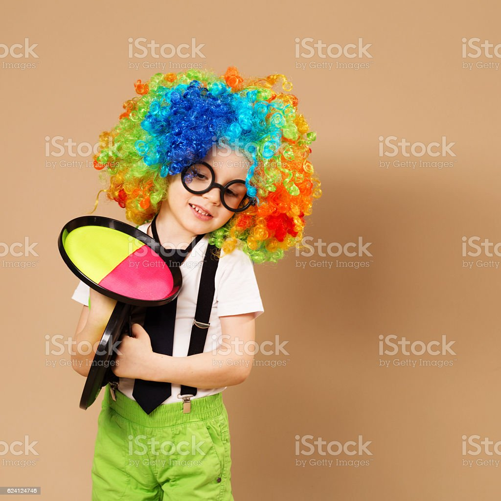 Kid in clown wig and eyeglasses playing catch ball game stock photo