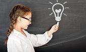 Kid in glasses with idea lamp on school chalkboard