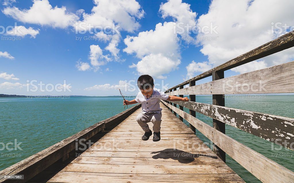 Kid Jumping on Wharf. stock photo