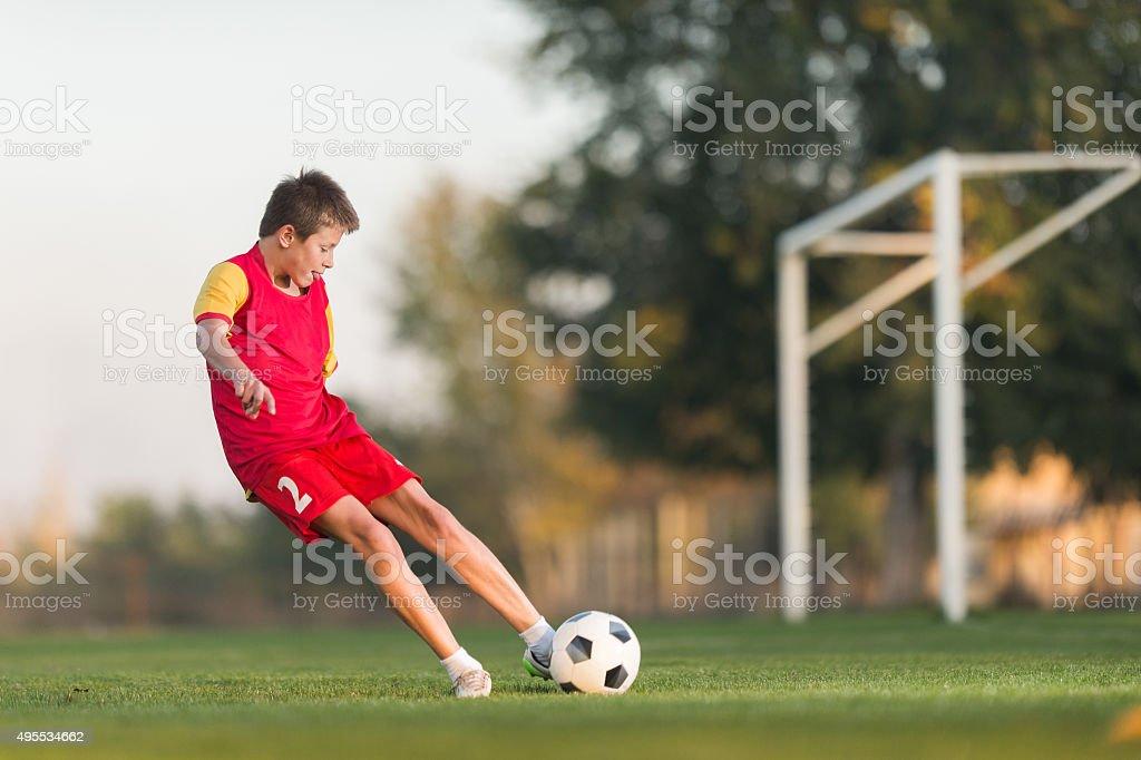kid kicking a soccer ball stock photo