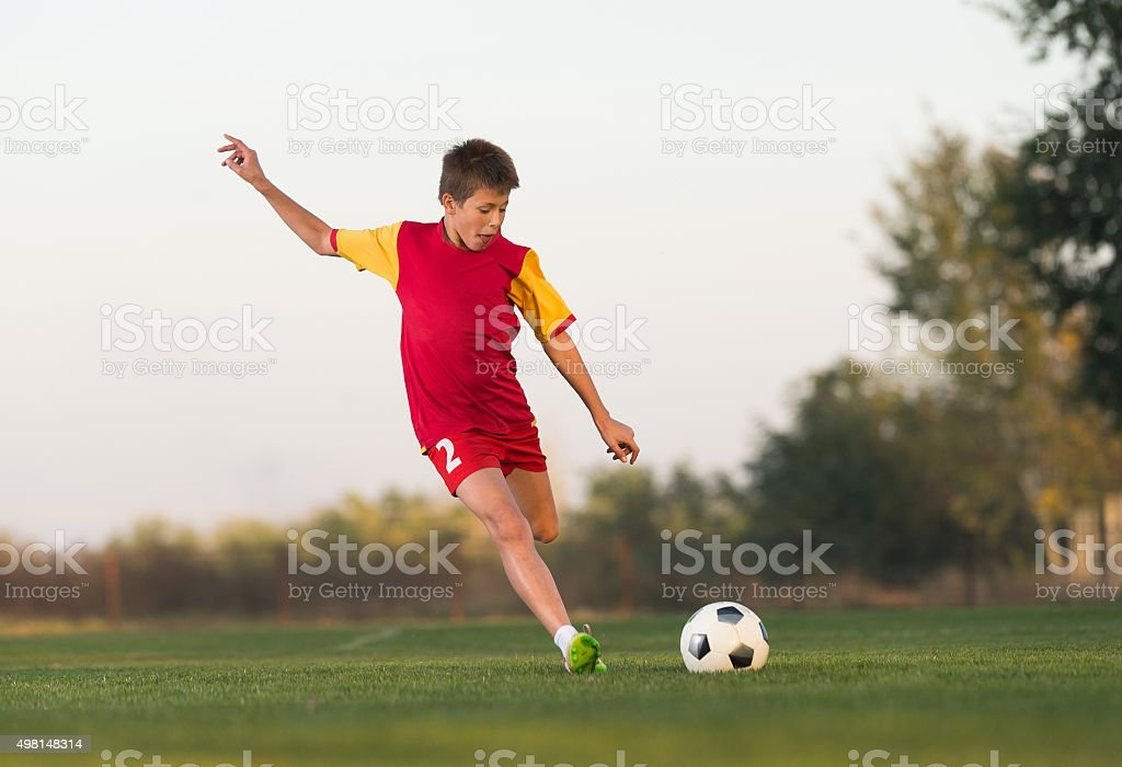 kid kicking a soccer ball stock photo