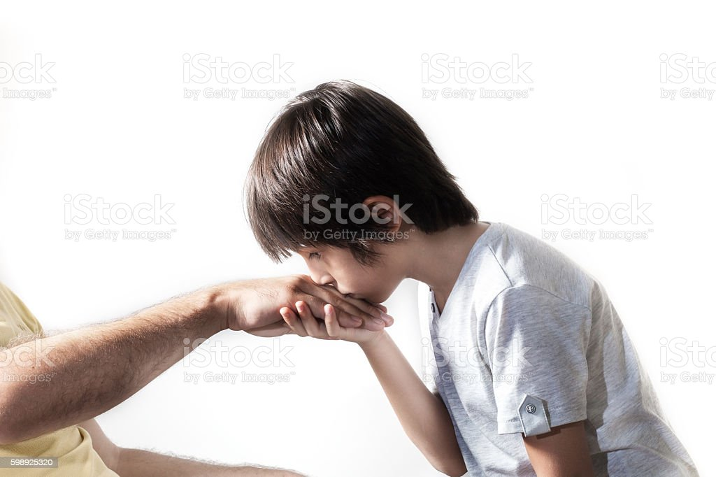 Kid kissing parent's hand stock photo