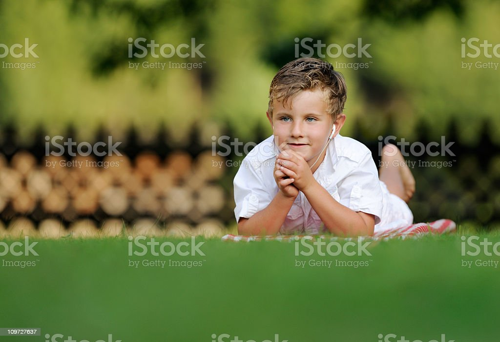 Kid lying in the back yard listening to Music (XXXL) royalty-free stock photo