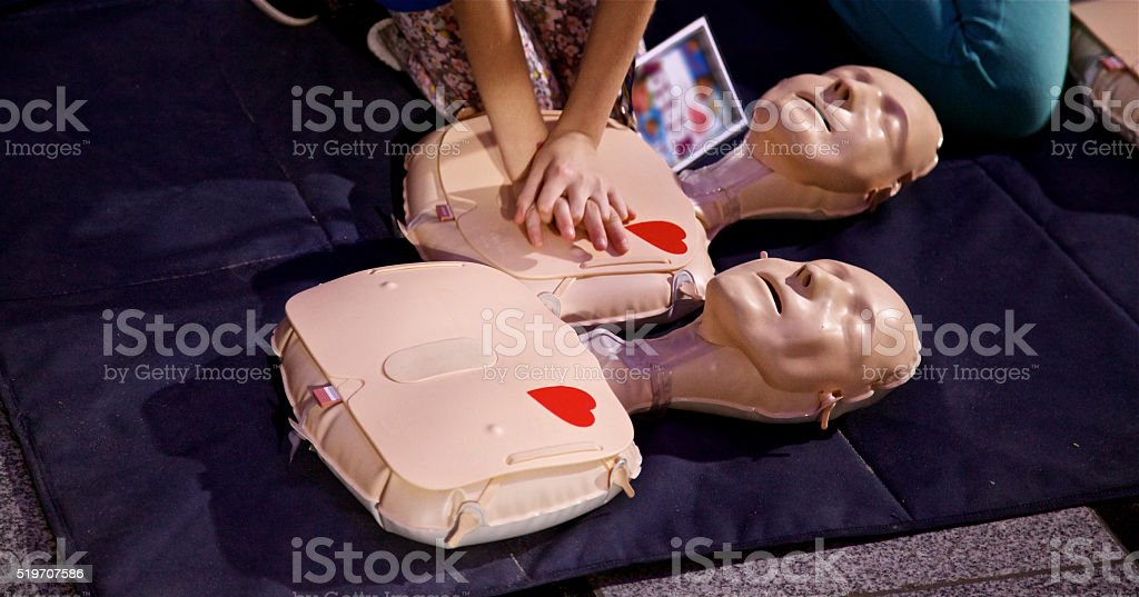 Kid make CPR Hospital mannequin. Medical industry equipment. stock photo