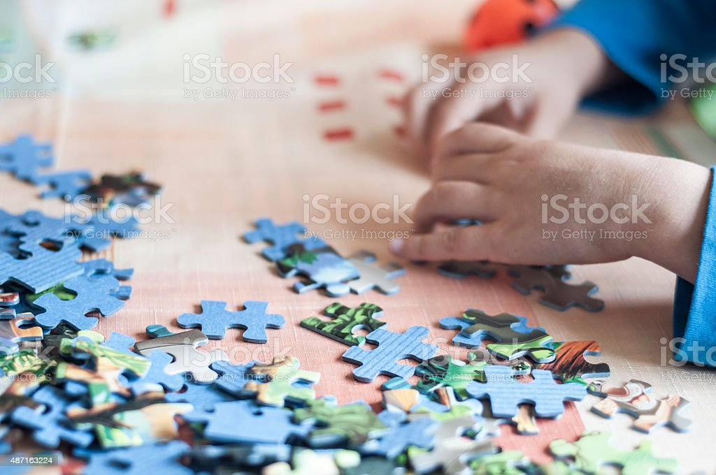 kid making puzzle stock photo