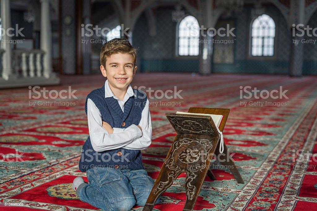 kid near holy koran stand stock photo