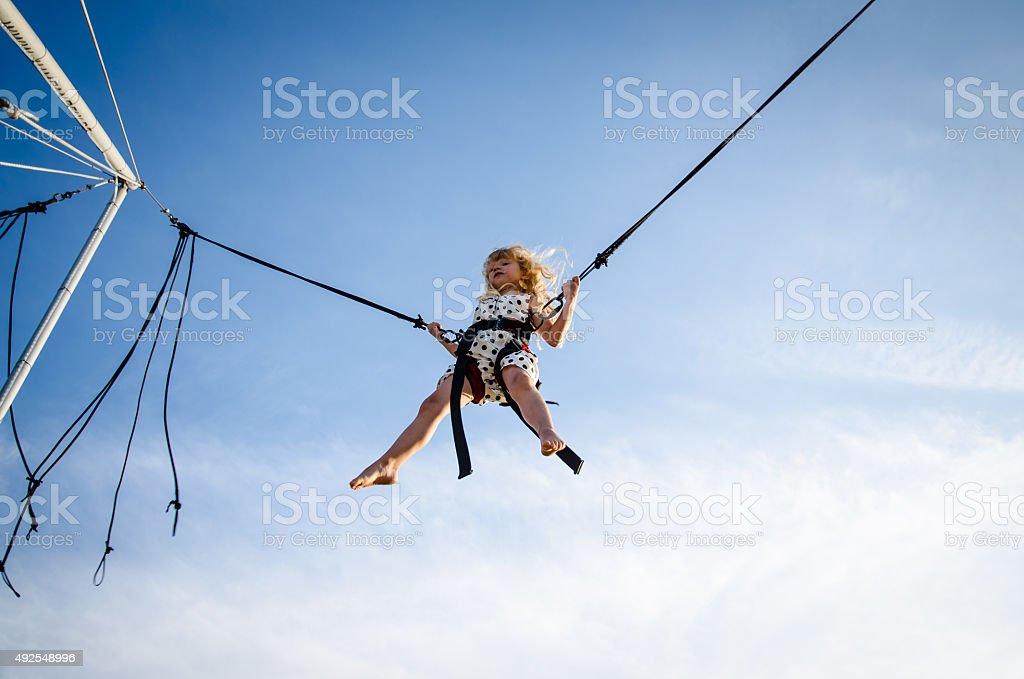 kid on jumping attraction stock photo