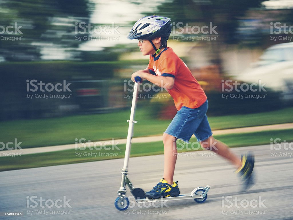 kid on pushing scooter stock photo