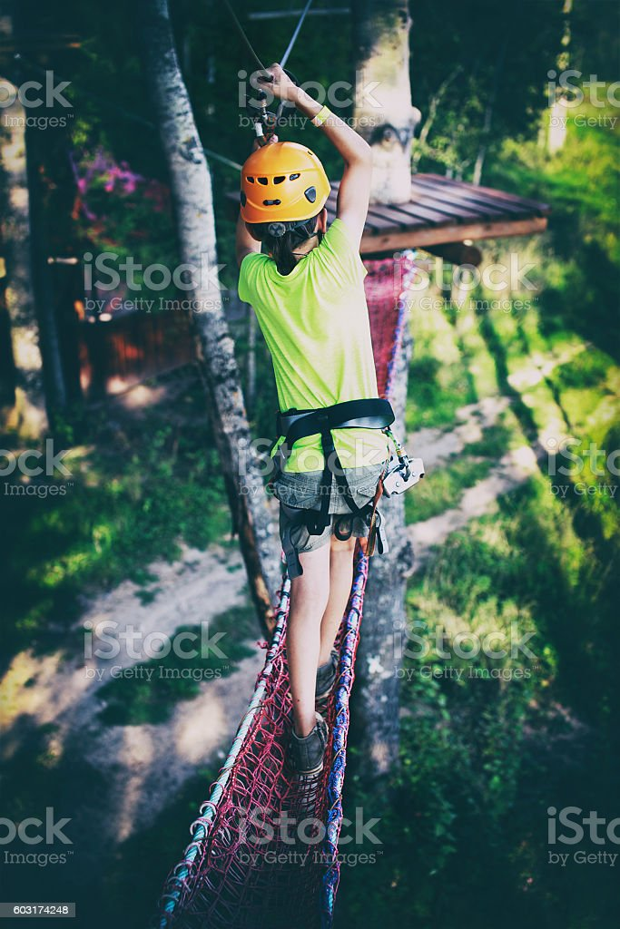 kid passes a rope obstacle course high above the ground stock photo