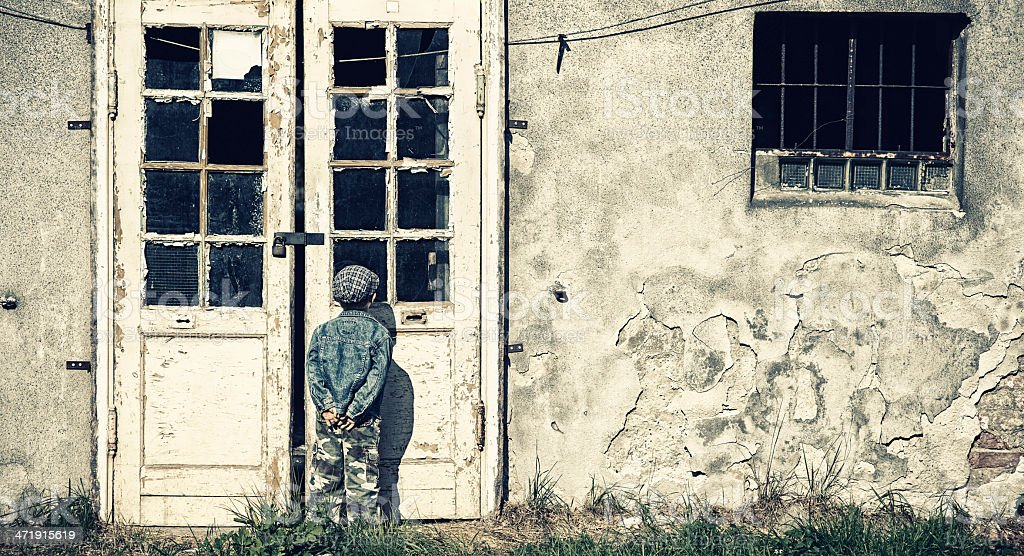 Kid peeping into ruined house royalty-free stock photo
