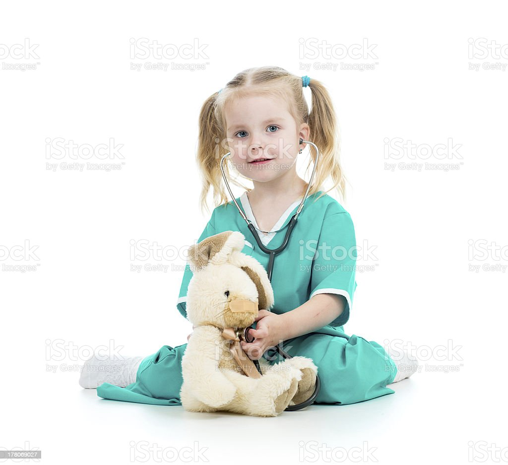 kid playing doctor and examining toy stock photo