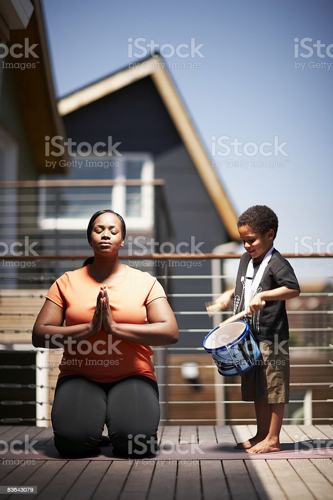 kid playing drum,while mother practices yoga stock photo