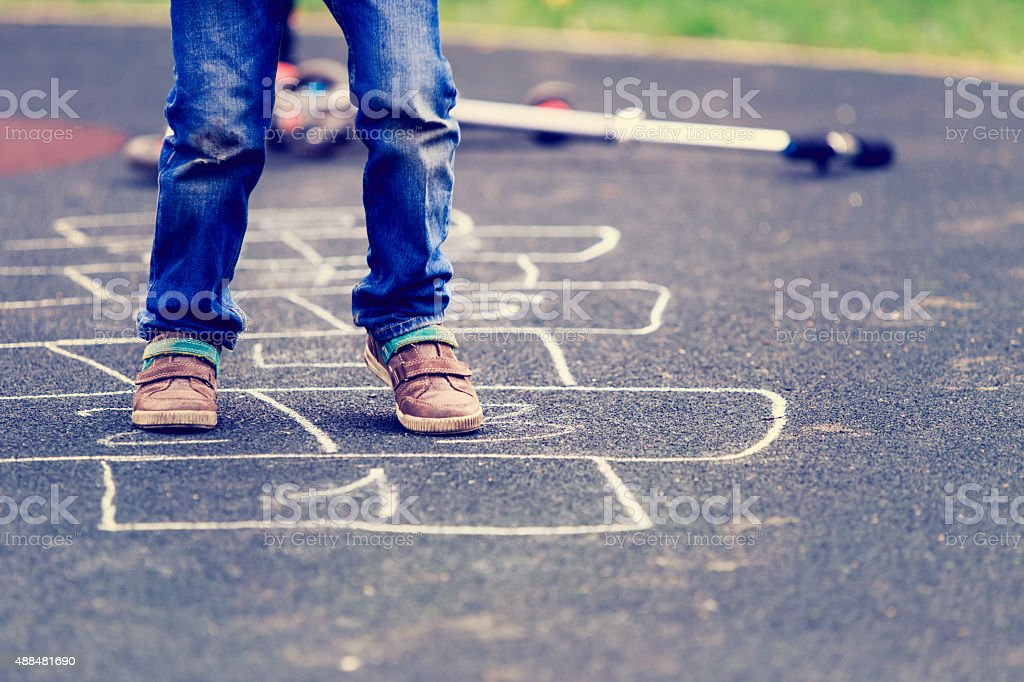 kid playing hopscotch on playground outdoors stock photo