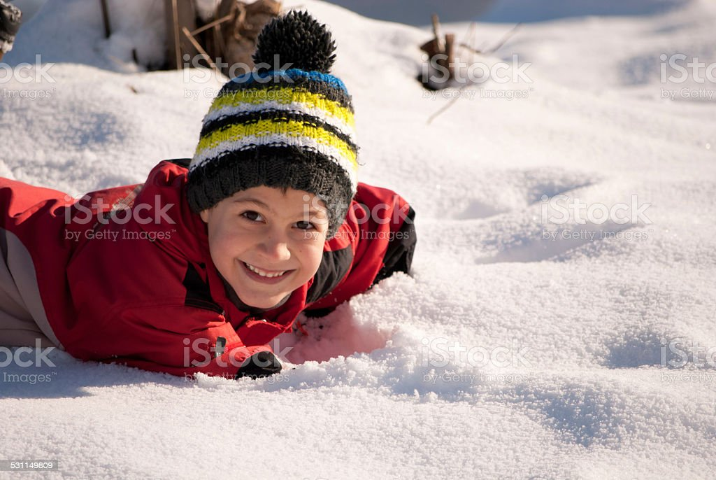 Kid playing in snow stock photo