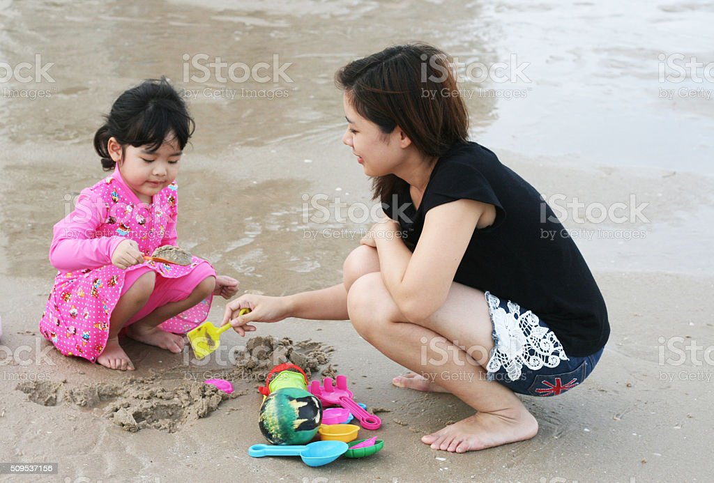 Kid playing sand with mom on the beach stock photo