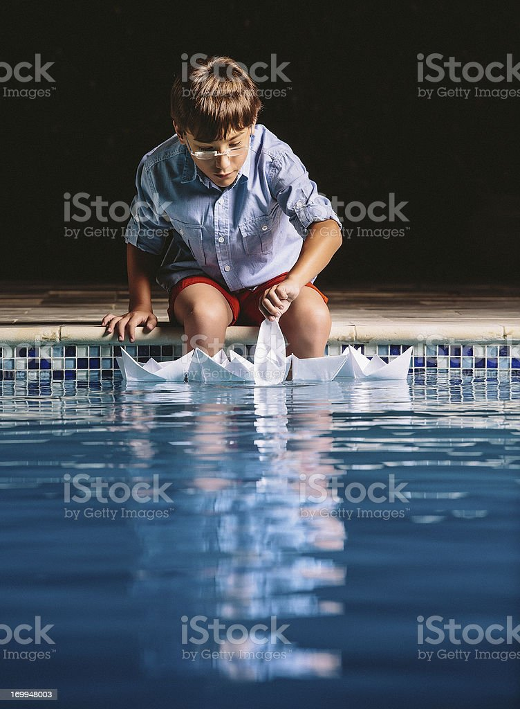 kid playing with paper boats royalty-free stock photo
